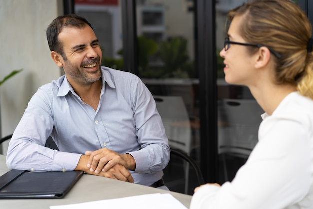 Cheerful mid adult hr manager having interview with candidate