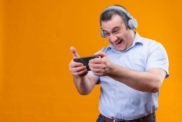 Веселый мужчина среднего возраста в синей полосатой рубашке играет на мобильном телефоне в наушниках стоя