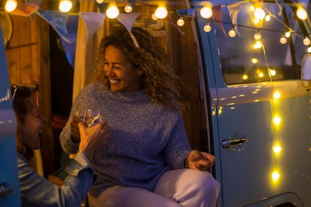 陽気な中年女性は、古典的なバンの中で屋外に座り、黄色い電球でワインを飲むナイトライフを楽しむ