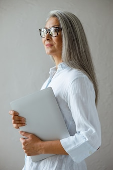 Cheerful middle aged asian business lady wearing stylish shirt holds modern laptop standing near grey stone wall in studio side view