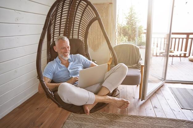 Веселый кавказский бизнесмен средних лет в повседневной одежде, сидя с ноутбуком на кресле-качалке в