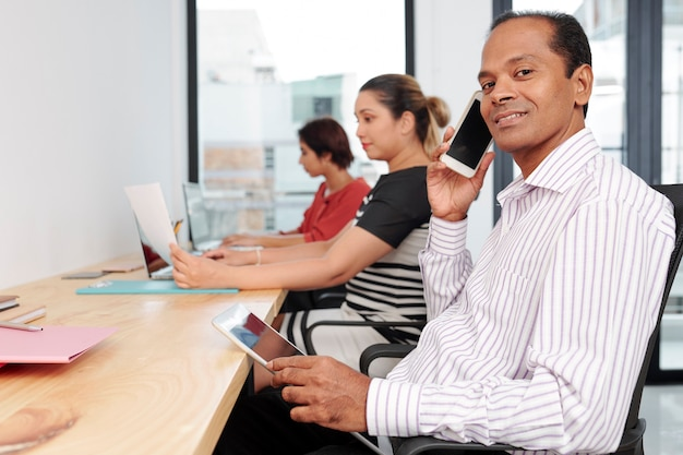 Веселый индийский предприниматель средних лет с планшетным компьютером сидит за большим столом с коллегами и звонит по телефону