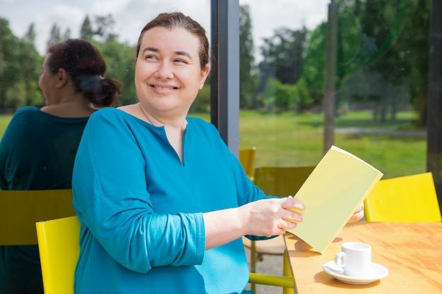 Cheerful middle aged lady spending her morning in coffee shop