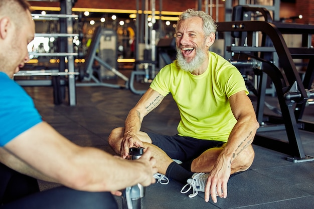 Cheerful middle aged man holding bottle of water discussing something with fitness instructor or