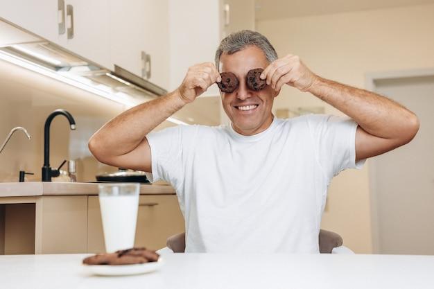 Веселый мужчина средних лет держит печенье возле глаз
