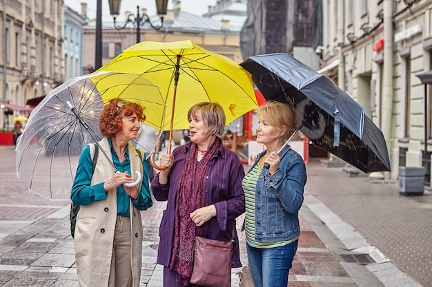 Cheerful middle-aged pretty women with colorful umbrellas are talking while walking during rainy weather on city street.