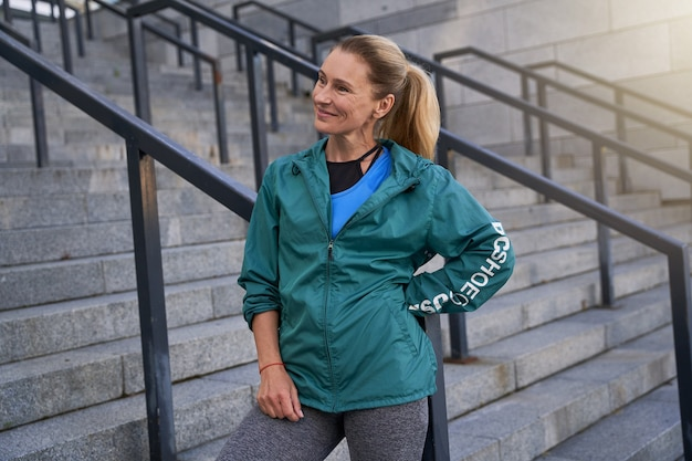 でトレーニングした後、屋外に立って微笑んでいるスポーツウェアの陽気な中年のスポーツウーマン