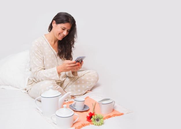 ベッドで朝食をとっている陽気な中年女性