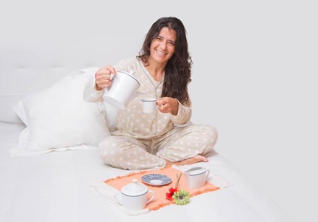 Веселая женщина средних лет, завтракающая в постели