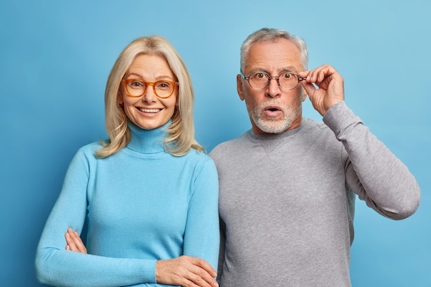 Cheerful middle aged woman and her husband pensioner reacts on shocking news keeps hand on spectacles isolated over blue wall