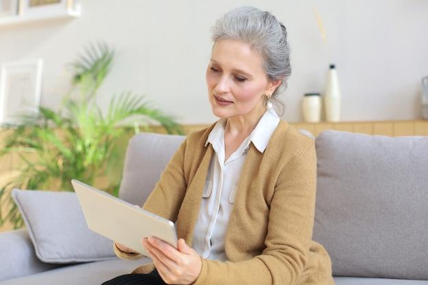Веселая женщина средних лет сидит на диване, использует компьютерные планшетные приложения, смотрит на экран, читает хорошие новости в социальной сети, делает покупки или болтает в интернете.