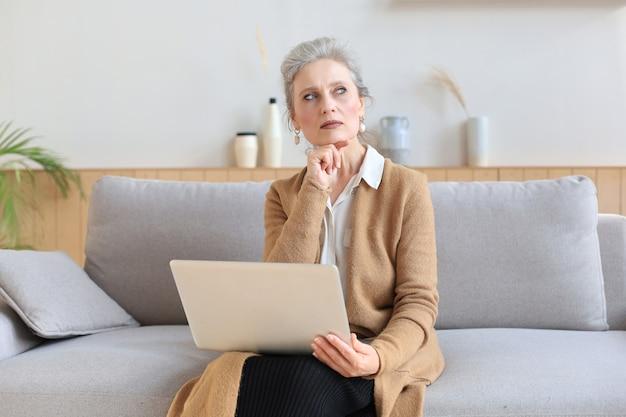 Веселая женщина средних лет с помощью ноутбука, сидя на диване у себя дома.