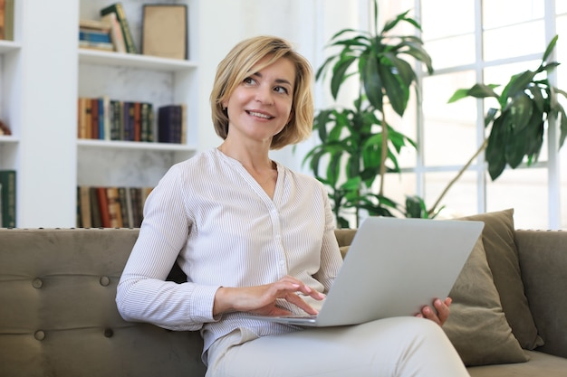 Cheerful middle aged woman using laptop while sitting on sofa at home.