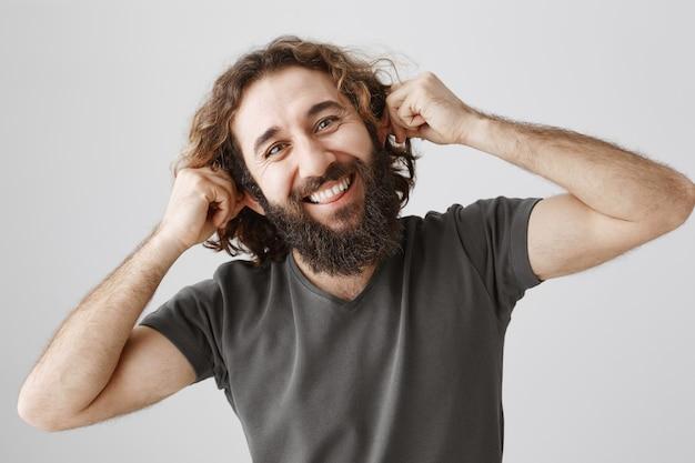 陽気な中東の男が遊び心のある耳を引っ張る、誰かをからかう