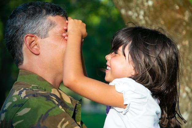 陽気な軍の父は、うれしそうな女の子が彼を閉じて笑っている間、小さな娘を腕に抱いています。側面図。家族の再会または帰国の概念