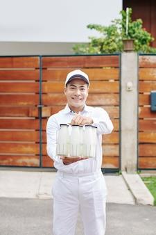 Веселый доставщик молока улыбается