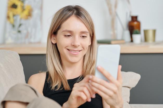 긴 금발 머리를 가진 쾌활한 밀레니엄 세대는 온라인 비디오나 친구의 사진을 스크롤하면서 스마트폰 화면을 보고 있습니다.