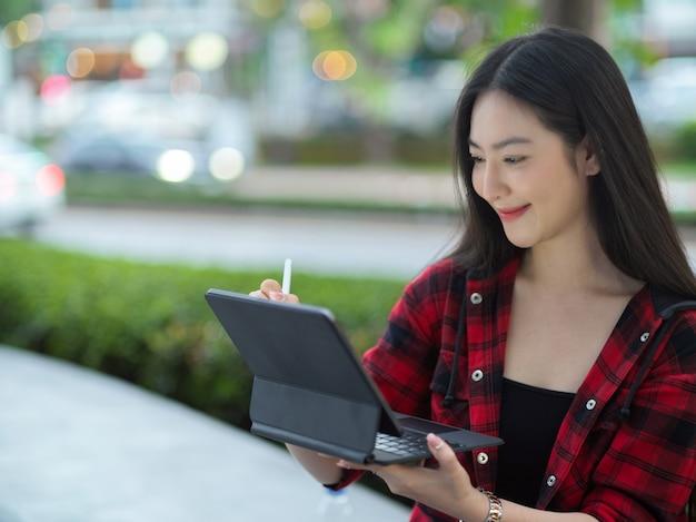 Жизнерадостная женщина-миллениал с помощью портативного планшета со стилусом сидит на городской улице