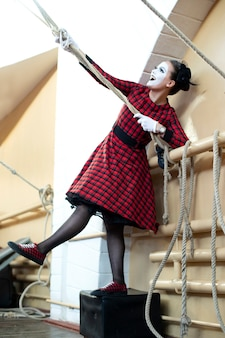 Cheerful mime girl in red dress pulls rope