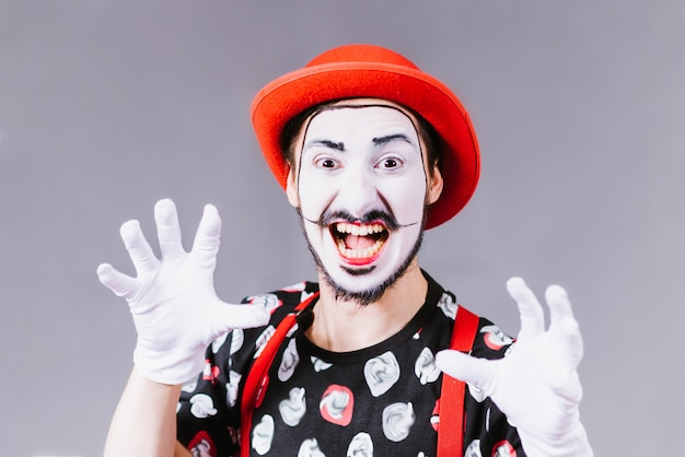 Cheerful mime posing and grimacing