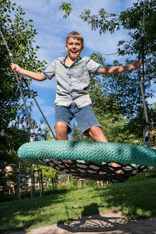 Cheerful and mischievous boy swinging on a public playground swing. kid play outdoors on warm sunny summer day.