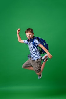 Cheerful mischievous schoolboy with glasses and a backpack jumps