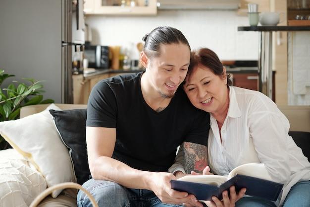 陽気な混血の成熟した母親と彼女の大人の息子が一緒に時間を過ごし、古いフォトアルバムの写真を見て
