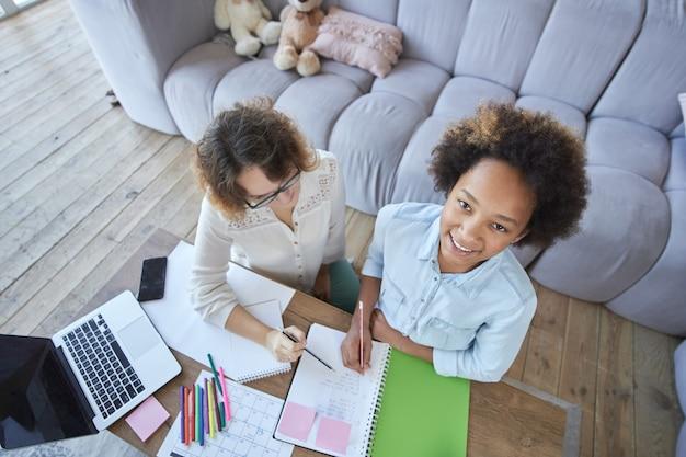 Веселая девушка-подросток смешанной расы улыбается в камеру, делая домашнее задание вместе с учительницей