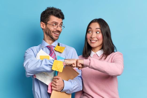 Веселые коллеги из смешанной расы, женщина и мужчина, празднуют успешное завершение работы, заставляют позу с бумажными документами с радостью смотреть друг на друга