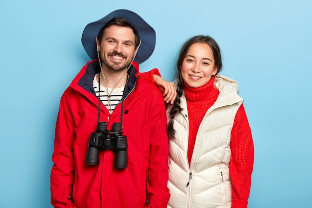 Cheerful mixed race woman and man smile joyfully, have recreation time, dressed in casual outfit, use binoculars for expedition, pose against blue wall