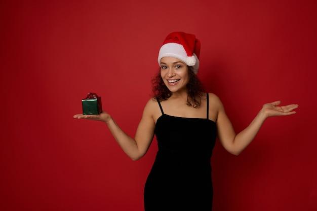 산타 모자를 쓴 쾌활한 혼혈 여성, 카메라를 바라보며 미소 짓고, 한 손에는 크리스마스 선물을 들고, 다른 손에는 빨간색 배경에 가상의 복사 공간을 들고 있는 손바닥을 들어 올립니다.