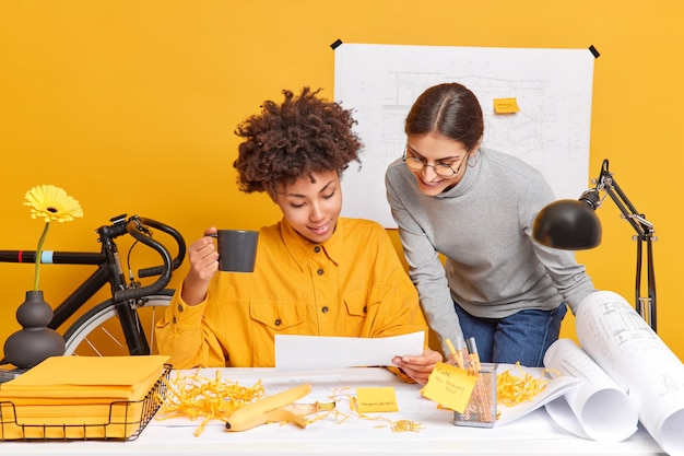 Cheerful mixed race women coworkers discuss ideas for project share opinion with each other prepare for presentation of architectural sketches for new building pose at desktop with papers around