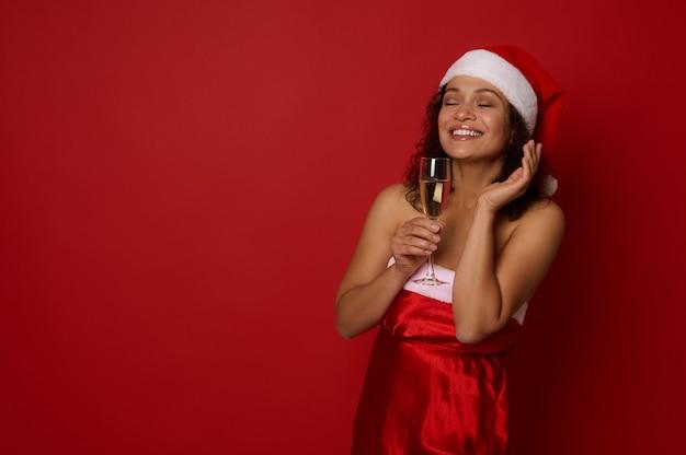 쾌활한 혼혈 젊은 여성은 아름다운 이빨 미소로 웃고, 산타 카니발 복장을 하고, 눈을 감고 포즈를 취하고, 샴페인이 든 플루트를 들고, 복사 공간이 있는 빨간색 배경 위에 격리되어 있습니다.