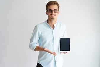 Cheerful mobile app developer in glasses showing tablet screen and looking at camera.