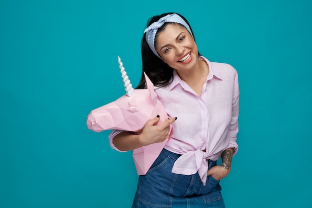 Cheerful model posing, holding pink paper unicorn head.