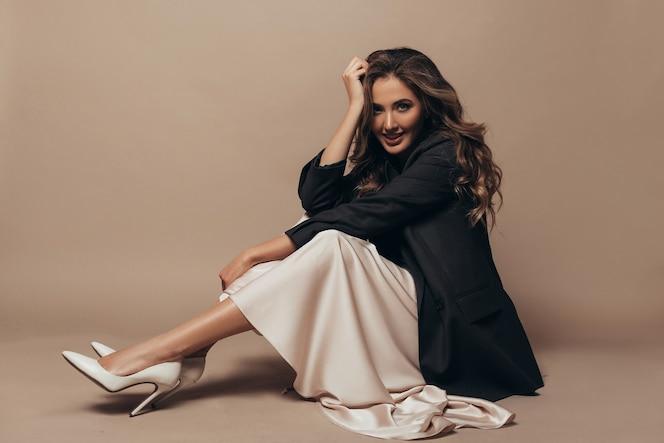 쾌활한 모델이 바닥에 앉아 현대적인 특대 블랙 재킷과 크림색 긴 드레스, 발에 하이힐 신발을 신고 있습니다. 곱슬 헤어 스타일과 메이크업
