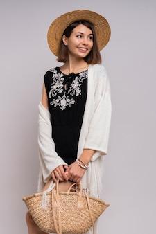 Веселая современная брюнетка женщина в летней одежде бохо и позирует в соломенной шляпе.