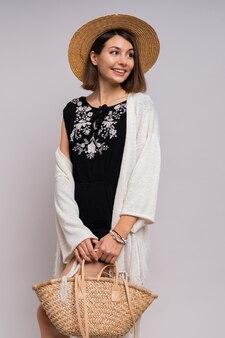 Donna castana moderna allegra in vestiti boho estivi e cappello di paglia in posa.