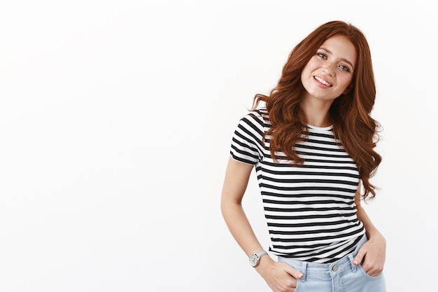 Cheerful modern caucasian redhead girl with freckles in striped t-shirt, holding hands in pockets, tilt head joyfully, curious, smiling look camera enthusiastic, talking casually, white wall