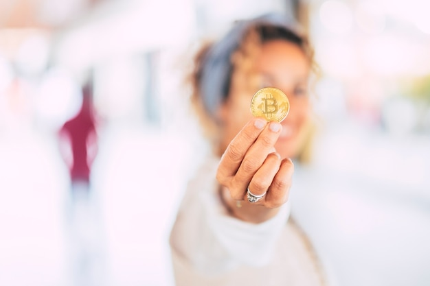 Cheerful modern caucasian woman in business world showing a gold bitcoin cryptocurrency for blockchain commerce trading concept for virtual money and new technology era