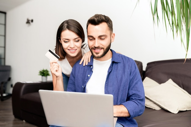 Веселая современная молодая пара в повседневной одежде сидит на диване и использует ноутбук и неограниченную кредитную карту, вместе делая покупки в интернете