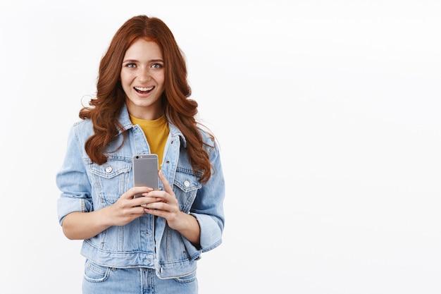 Allegra giovane donna moderna in giacca di jeans, tiene in mano lo smartphone e sorride ottimista, scatta foto nuovo telefono, messaggistica, muro bianco in piedi