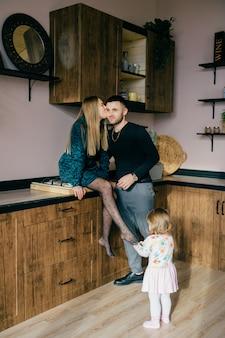 陽気なママとパパは、小さな子供と一緒にキッチンで時間を過ごします。