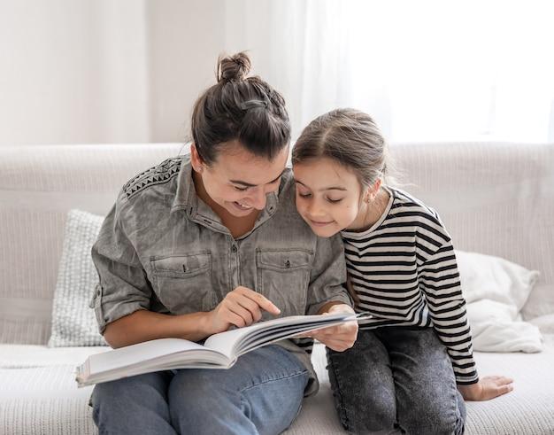 Веселая мама и дочка отдыхают дома, вместе читают книгу. концепция счастливой семьи и дружеских отношений. Premium Фотографии