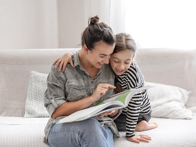 Веселая мама и дочка отдыхают дома, вместе читают книгу. концепция счастливой семьи и дружеских отношений.
