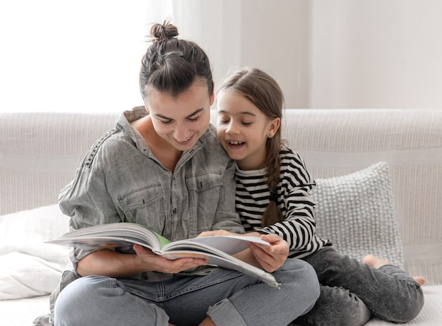 陽気なお母さんと娘が一緒に本を読んで、家で休んでいます