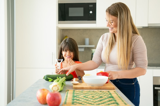 陽気なママと娘が夕食に野菜を作りながら楽しんでいます。少女と彼女の母親は、キッチンカウンターでサラダの野菜をはがしてカットし、おしゃべりして笑っています。家族の料理のコンセプト