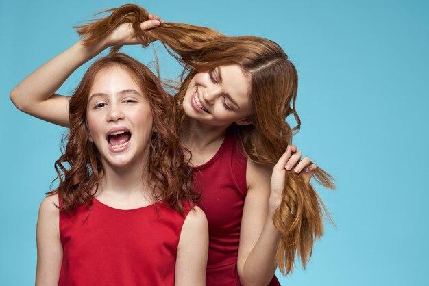 陽気なママと娘は喜びのライフスタイルコミュニケーション友情青い背景を抱擁します