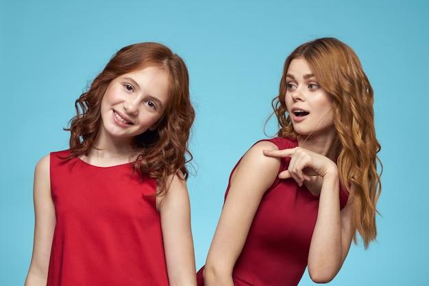 陽気なママと娘は喜びライフスタイルコミュニケーション友情青い背景を抱擁