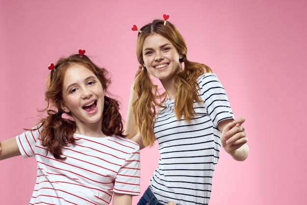 楽しいストライプのシャツを着た陽気なママと娘